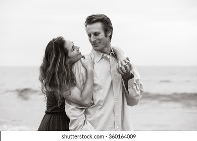 Attractive couple at beach looking into each other's eyes. B&W