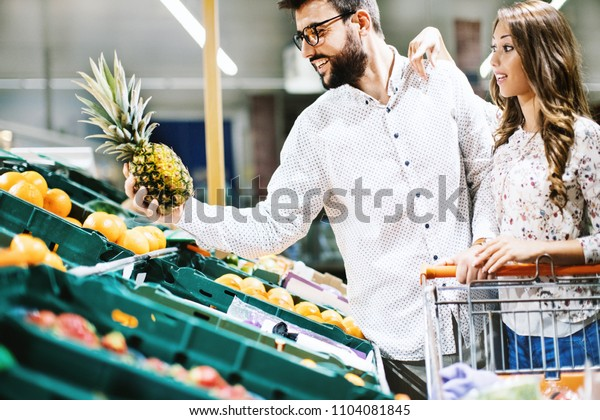 Attractive couple buying pineapple at a grocery store. Side view. Horizontal.