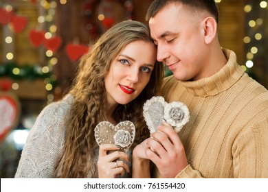 attractive couple celebrate valentine's day. they hugging, smiling and holding hearts- symbols of love in hands. Concept of happy valentine's day