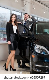 attractive couple chooses the black car in the showroom