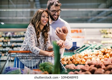 Attractive couple choosing fresh potatoes in a supermarket. Side view. Horizontal.
