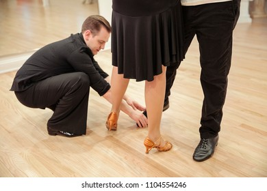 attractive   couple dancing in dance studio. instructor showing position of leg