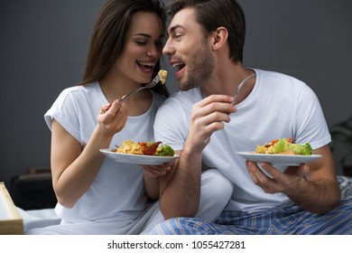 Attractive couple eating scrambled eggs in bed
