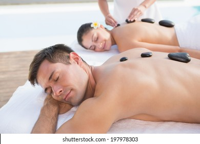 Attractive couple enjoying hot stone massage poolside outside at the spa