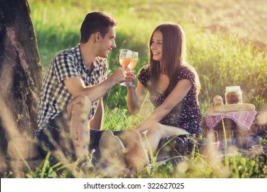 Attractive Couple Enjoying Romantic Sunset Picnic in the Countryside / Vintage style photo with custom white balance, color filters and soft focus effect,
