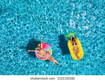A attractive couple enjoys the hot summer day on colorful, inflatable floats over blue pool water