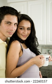 An attractive couple enjoys the morning with a kiss and a hot cup of coffee or tea.