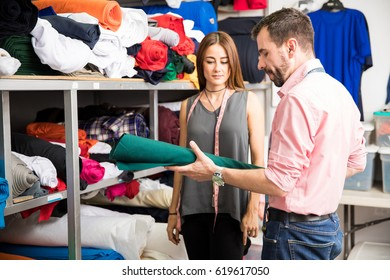 Attractive couple of fashion designers trying to choose the right fabric for their new project