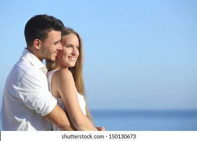 Attractive couple flirting and cuddling looking ahead with the sea in the background