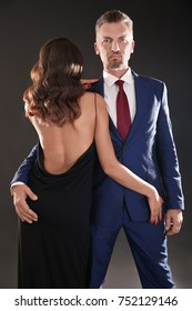 Attractive couple in formal wear on black background