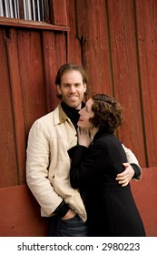 An attractive couple in front of rustic red barn