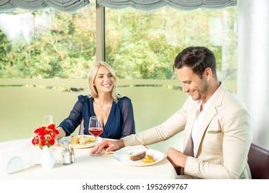 Atractiva pareja que come en el restaurante del hotel