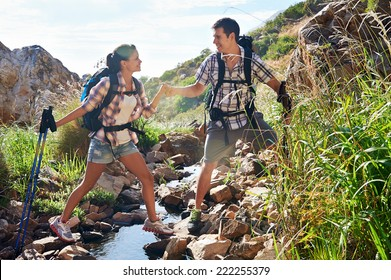 An attractive couple holding hands as the man helps his girlfriend across the stream of their hiking trail