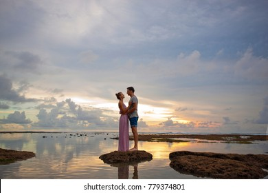 Attractive Couple Hugging During Sunset Near the Ocean. Honeymoon Vacation Concept.