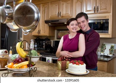 Attractive couple hugging in the kitchen by a counter covered with a cake and a present. The pair are laughing heartily while looking at the camera. Horizontally framed shot.