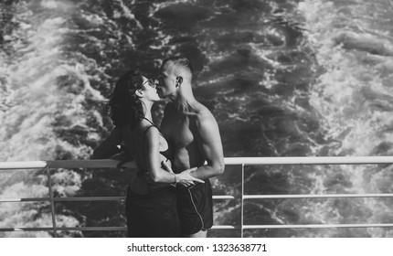 Attractive couple kissing and enjoy summer vacation. Honeymoon, just married concept. Couple stands on deck of cruise liner with sea waves on background. Couple in love travelling on cruise ship.