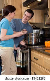 Attractive couple in the kitchen smiling at each other while standing by the stove. Vertically framed close-up shot.