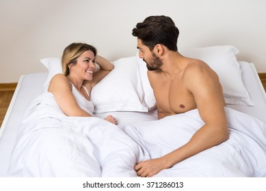Attractive couple laying in bed and talking.