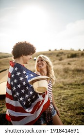 An attractive couple in love wrapped in american flag enjoying in front a tent at the campsite.