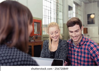 Attractive couple in a meeting with a broker or agent sitting across the desk from her smiling as they read through a presentation