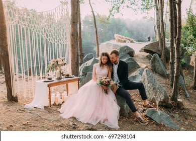 Attractive couple newlyweds, happy and joyful moment. Man and woman in festive clothes sit on the stones near the wedding decoration in boho style. Ceremony outdoors.