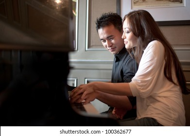 Attractive Couple playing piano
