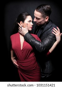 Attractive couple of professional dancers dancing passionate tango on dark background