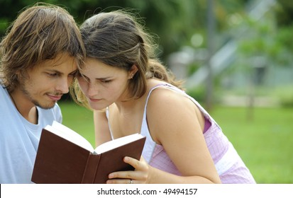 Attractive couple read together in the park