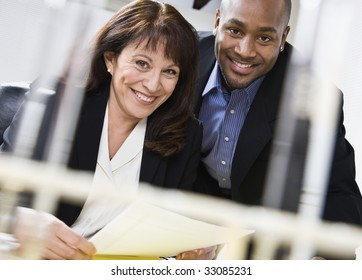 Attractive couple reading paper. Male above female, in business suits. Horizontal.