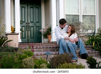 An attractive couple relaxing in front of their home