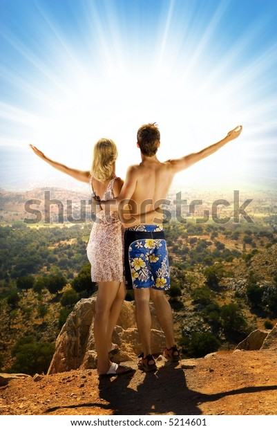 An attractive couple relaxing in high mountains and watching sunrise