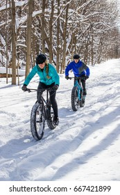 An attractive couple rides their fat bikes on a trail in the snow.