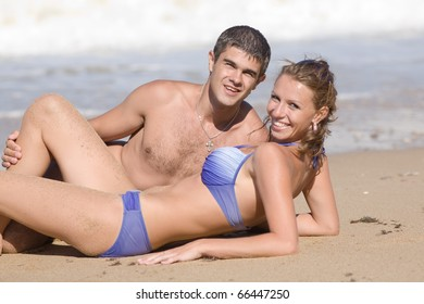 Attractive couple at the sea. Young man and young woman on the beach
