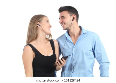 Attractive couple sharing music with a headphones isolated on a white background