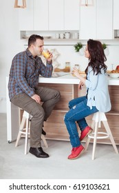 Attractive couple sitting having juice together and laughing at home in kitchen.