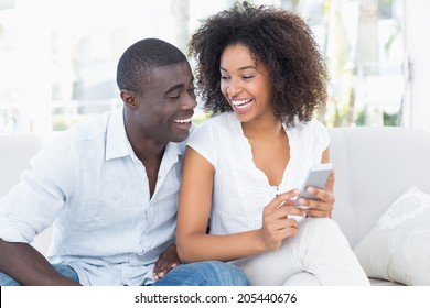 Attractive couple sitting on couch together looking at smartphone at home in the living room