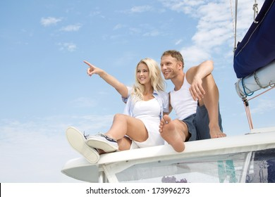 Attractive couple sitting on sailing boat - love.