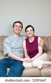 Attractive couple sitting on their living room couch with their arms around each other. Both are smiling at the camera. Vertically framed shot.