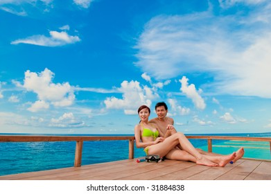 An attractive couple sitting on a wooden boat in the ocean