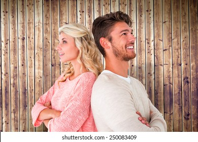 Attractive couple smiling with arms crossed against wooden planks