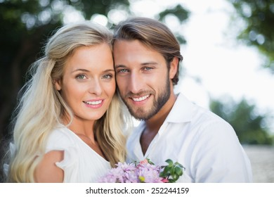 Attractive couple smiling at camera on a sunny day in the city