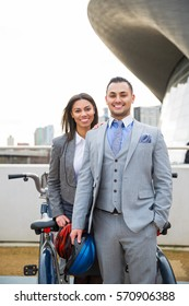 Attractive couple standing near bicycle docking station.