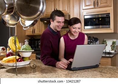 Attractive couple standing in their kitchen and reviewing something on their laptop screen together. Both are laughing and looking at the screen. Horizontally framed shot.
