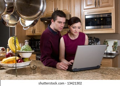 Attractive couple standing in their kitchen and reviewing something on their laptop screen together. Both have serious expressions and are looking at the screen. Horizontally framed shot.