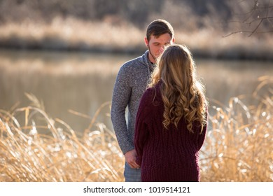 Attractive couple talking, her back is to the viewer. He is facing the viewer.