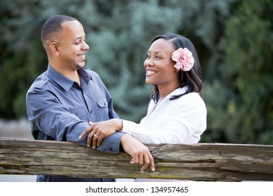 Attractive couple talking and smiling in a pretty park setting