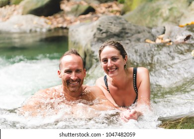 Attractive couple under jungle waterfall
