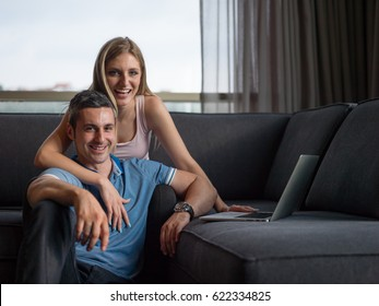 Attractive couple using a laptop in the living room