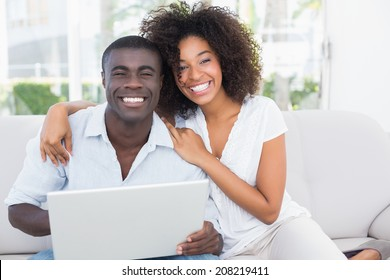 Attractive couple using laptop together on sofa at home in the living room