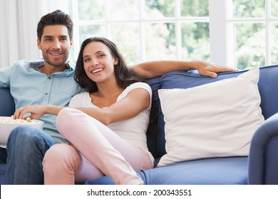 Attractive couple watching tv on the couch at home in living room